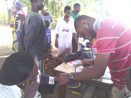 Dr. Ebenezer taking blood pressure during medical outreach